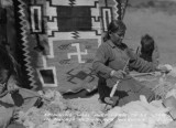Spinning wool into yarn to be used in Navajo Indian rug weaving