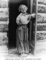Child in doorway of log cabin
