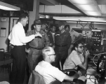 Group of U.S. Army officials visiting  men in a Honeywell equipment room