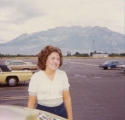 Unidentified woman standing in a parking lot.