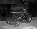 Ab Jenkins sitting on a tractor in Salt Lake City, Utah, circa 1920s-1930s.