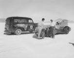"Ab Jenkins next to his racing vehicle the ""Mormon Meteor"" on the Bonneville Salt Flats..."