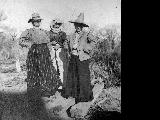 """Do you know them?""  Three unidentified women wearing men's hats and dressed-up"