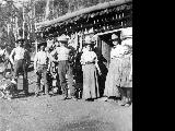 """McPherson Camp, August 1910.""  Men and women gathered in front of a worn log cabin. ..."