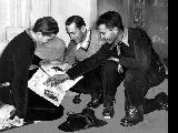 Jack Reddish, Dev Jennings and Dick Movitz looking at a magazine article