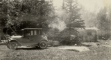 [old car in front of log cabin]