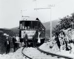 "[Men standing behind railway car or trolley on which is hanging a sign ""Over the Lofty..."