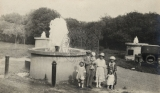 [Family standing next to a fountain.]