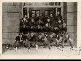 Football team on the steps of a building.