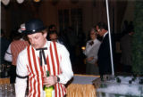75th Anniversary - A wine server dressed in red stripes
