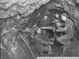 Miners working with a drill