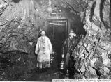 Two miners underground with lanterns