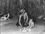 Navajo woman and baby eat ceremonial meal after destruction of painting July 1945