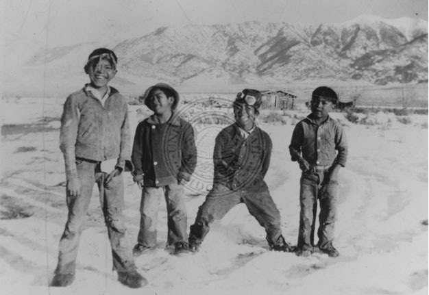 Four young boys playing in the snow;