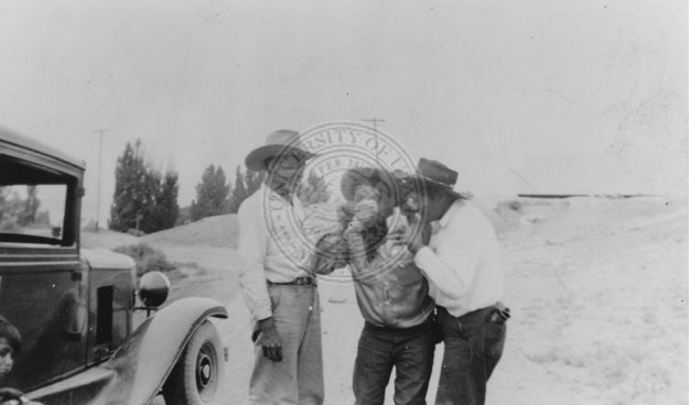 Three men standing near a car drinking from a bottle.
