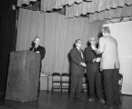Four officials on stage of the Intermountian School auditorium;