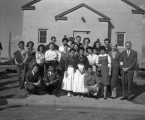 Group of people standing in front of the church on the Intermountain School campus;