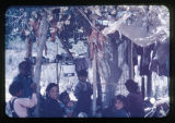 A group of women and children sitting under a canopy.  One of the women is weaving.