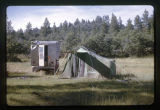 A green tent and a trailer on a camping trip;