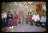 A group of Navajo men sitting under a canopy of blankets;