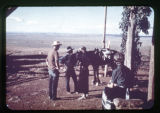 A priest talking to Navajo cowboys with horses.