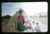 A Navajo family posed in front of Hogan.