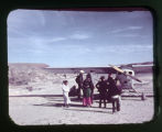 Father Liebler with a group around an airplane;