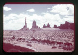 Desert landscape; three men driving horses across Monument Valley.
