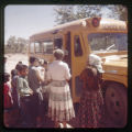 Children going into a school bus. Two women standing next to the bus.