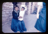 Navajo woman wearing a blue dress, holding up her baby in a papoose.