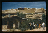 Group of Navajos standing in front of a stone home. Mesas in the background.
