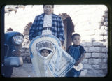 Navajo mother with two children; infant in papoose and a toddler standing next to toddler.