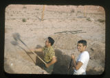 This is a photograph of two men digging a large hole in the ground. The man to the left is wearing...