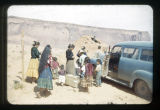 Group of Navajos standing near a blue car with the door open. Mesas in background.
