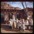 A group of children outside a building dressed as Pilgrims and Indians reenacting the Mayflower...