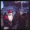 A man dressed as Santa Claus giving out candy canes.;