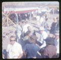 A crowd scene.  There is a red, white, and blue banner wrapped around a stand.  There is also a...
