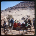 A group sitting at a table in the desert.;