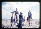 Father Liebler next to two men on horses.  One man is pointing his arm to the side of the image.