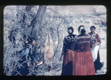Clinic dedication, food preparation. Four women standing next to a tree.  There is an animal...