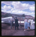 Father Liebler with a  group of people standing next to an airplane.