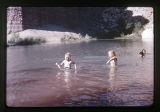 Four children swimming in the river.