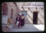 Catherine and Jeanette Pickett out in front of a building. The girl is sitting in a chair while...
