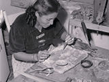 Navajo woman silversmith fits twisted wire to case of Zuni inlaid butterfly;