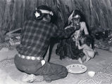 Navajo medicine man feeds ceremonial meal to female  patient [2];