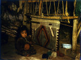 Navajo child in front of partially woven rug;