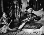 Navajo girls carding and spinning wool for rugs;